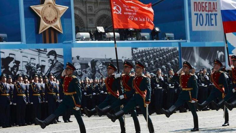 当地时间5月9日,俄罗斯举行盛大阅兵式庆祝卫国战争胜利70周年。图为俄罗斯国旗从受阅部队前经过。