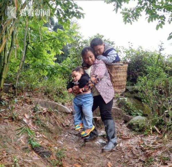 母亲郑琴背着两兄弟,从老家到学校的路上