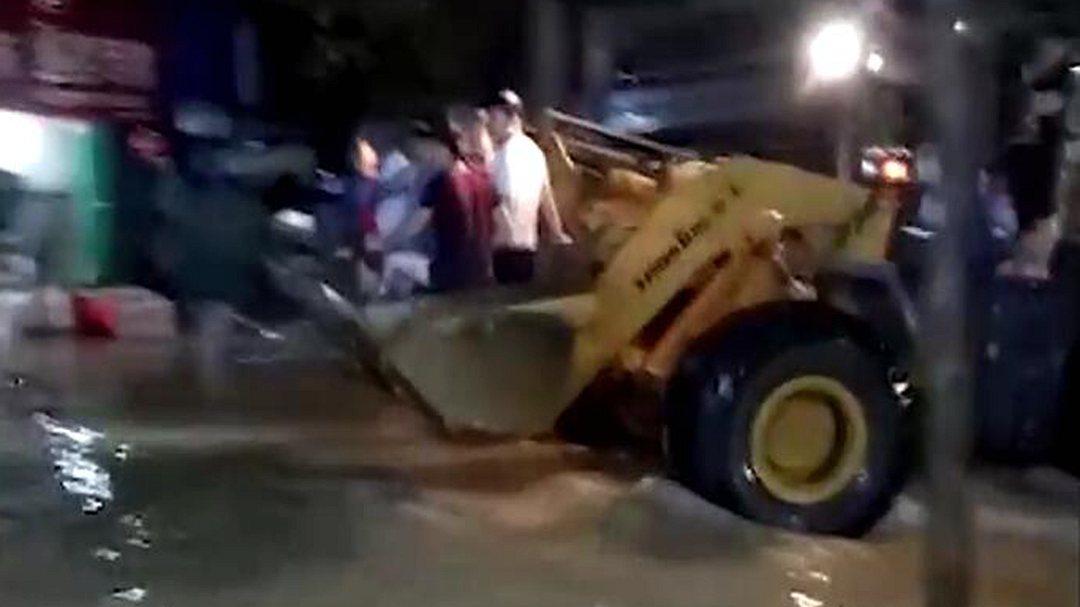 江西修水遭暴雨袭击街道被淹 市民乘铲车出行