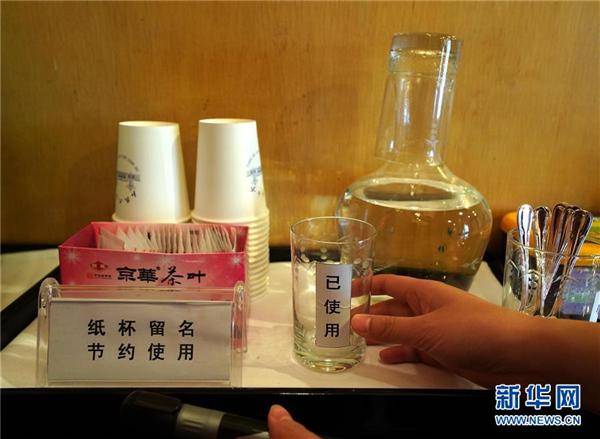 10月19日,北京人民大会堂的工作人员在记者工作间中整理水杯。新华社记者 陈建力 摄