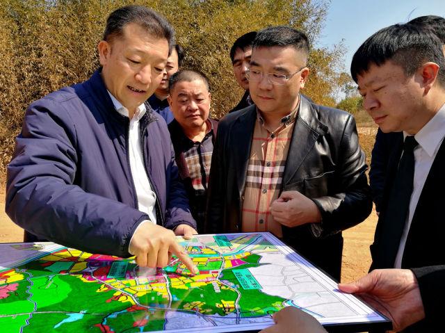 廖俊波(左一)向前来考察的企业代表介绍福建省南平市武夷新区发展规划(2017年2月15日摄 新华社发)。