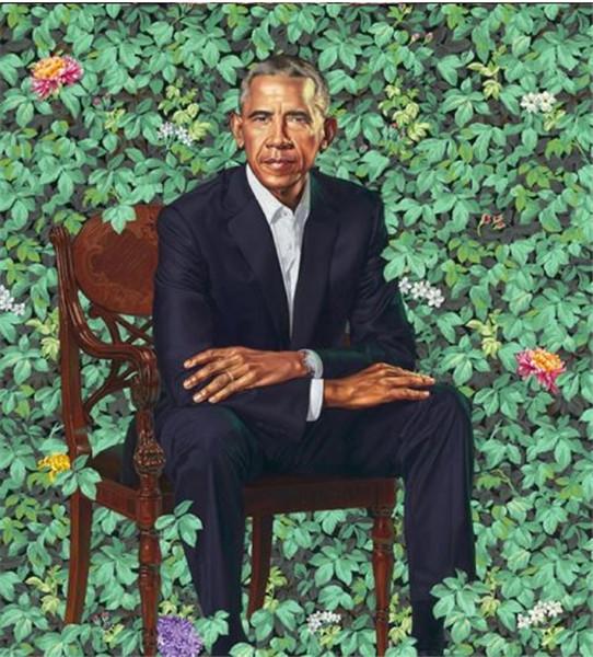 在绿叶红花的明媚背景下,奥巴马双手叠放在膝上,表情肃穆。
