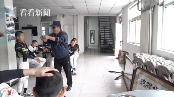 """""""师爷""""张锦新正在给爱心棒球基地里的孩子们讲解""""传承棒球魂""""的含义"""