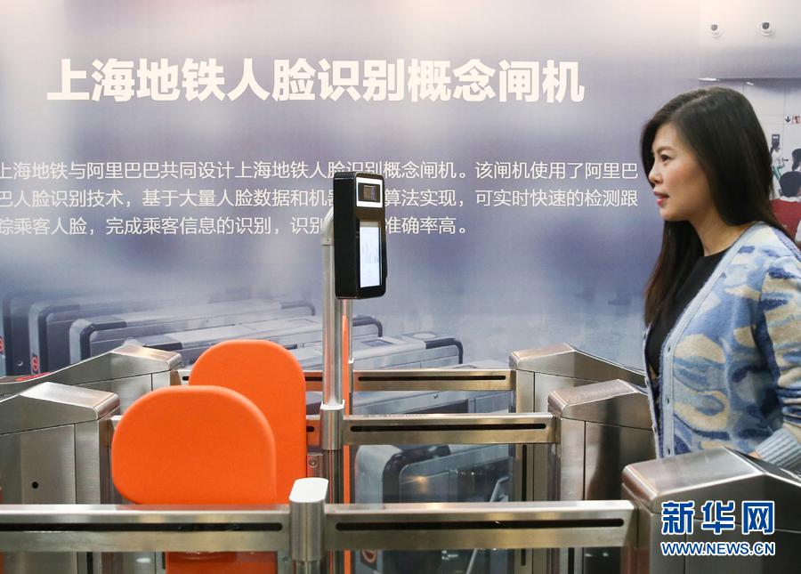 在上海申通地铁集团有限公司,工作人员在现场体验刷脸进站技术(2017年12月5日摄)。新华社记者 丁汀 摄