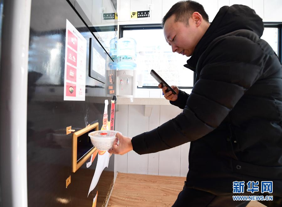 在位于西安曲江创客大街边的一家无人面馆内,市民用手机拍摄机器刚做好的面食(1月10日摄)。新华社记者 邵瑞 摄