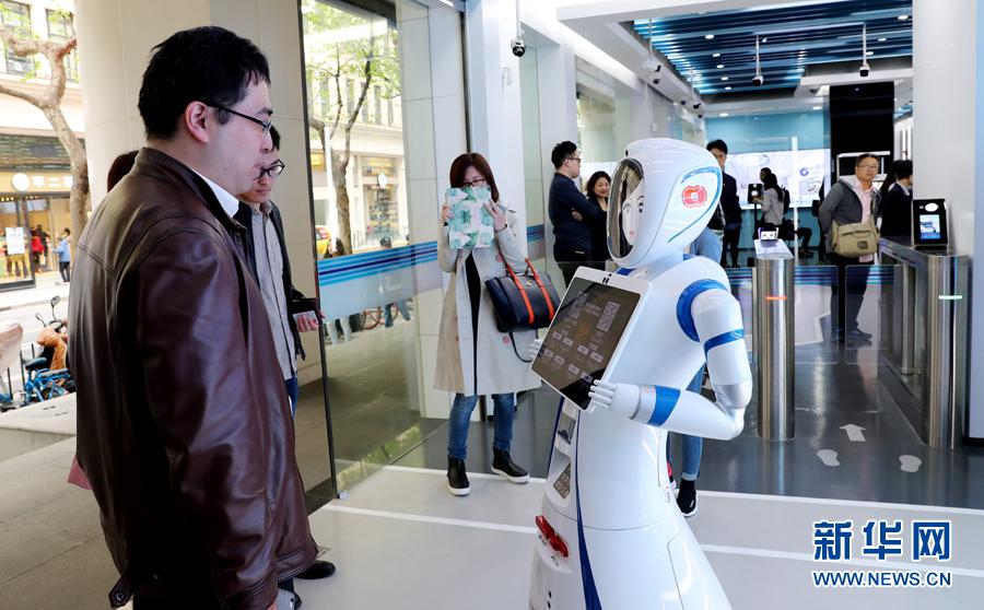 一位市民在位于上海九江路的无人银行入口处向迎宾机器人说明需要办理的业务种类(4月12日摄)。近日,中国建设银行在上海九江路开出国内首家无人银行。新华社记者 方喆 摄
