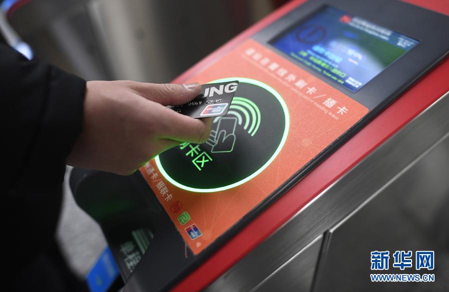 乘客在杭州地铁丰潭路站体验使用带有闪付功能的银联IC卡过闸乘车(2017年12月27日摄)。新华社记者 黄宗治 摄