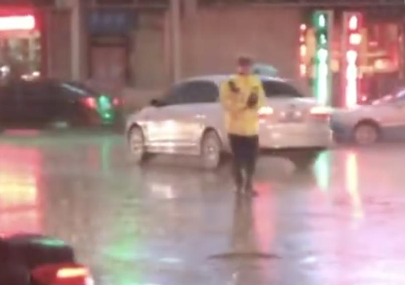 暖心!暴雨中美女为坚守的交警送伞后小跑离开