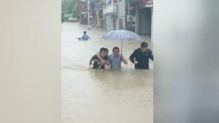 干得漂亮!六旬书记在齐腰深洪水中背起患病妇女
