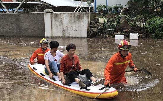 2018年5月7日,在积水严重的厦门市思明区东坪山路,消防官兵转移被困人员。
