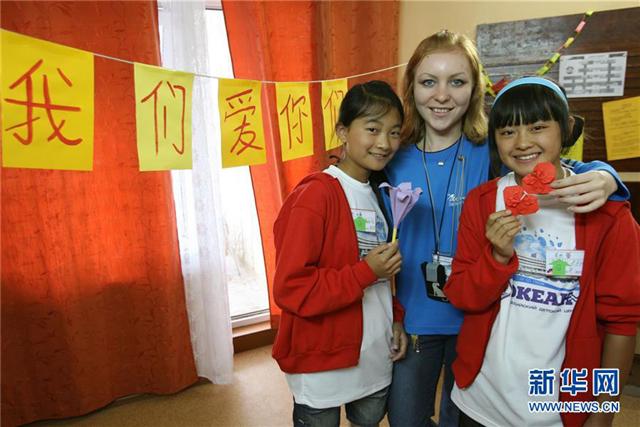 """2008年7月21日,在""""海洋""""全俄儿童中心,两个中国小姑娘和她们的折纸课老师合影留念。"""