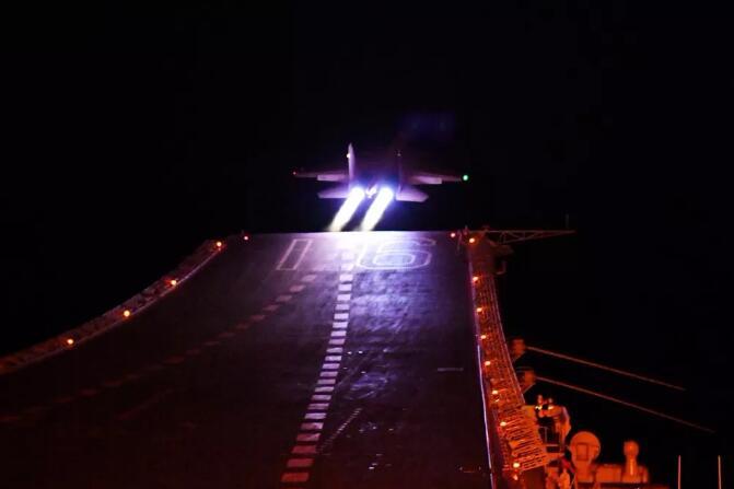 歼-15舰载战斗机进行夜间滑跃起飞训练