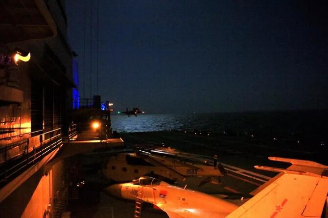 歼-15舰载战斗机进行夜间阻拦着舰训练。
