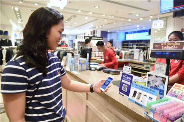 """2017年11月11日,在菲律宾马尼拉一家商场,消费者使用GCash电子支付系统付款。与阿里巴巴合作的GCash被称作""""菲律宾版支付宝""""。新华社记者秦晴摄"""