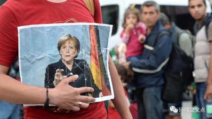 2015年9月一名难民到达慕尼黑后手拿默克尔照片