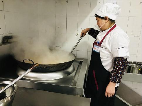 炊事员焦大翠正在给师生们做晚餐。