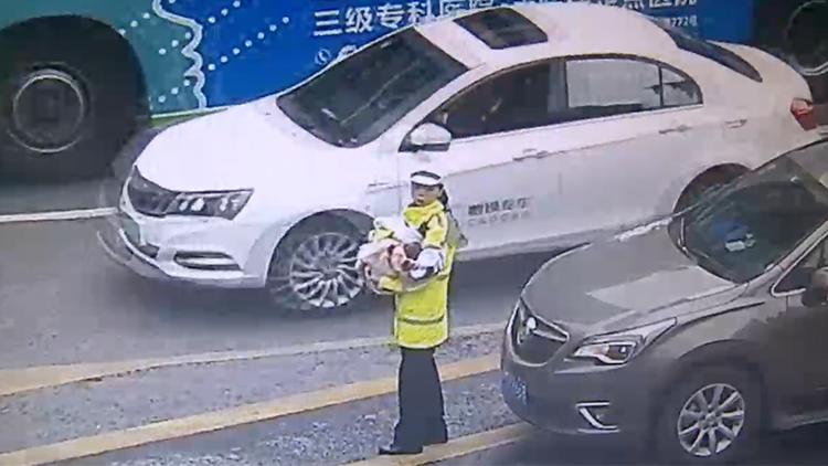女警抱着婴儿单手指挥交通?背后真相让人落泪