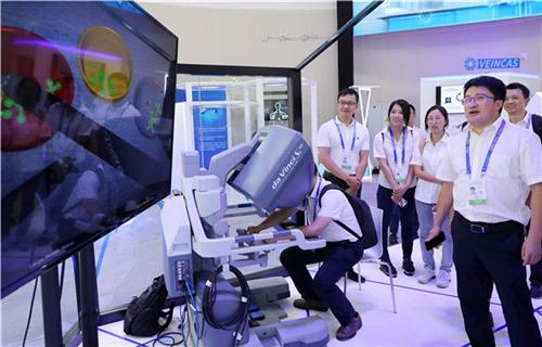 2018年9月17日,在上海举办的世界智能大会上,参观者在屏幕上观看一款机器人手术系统的作业演示。新华社记者 方喆 摄