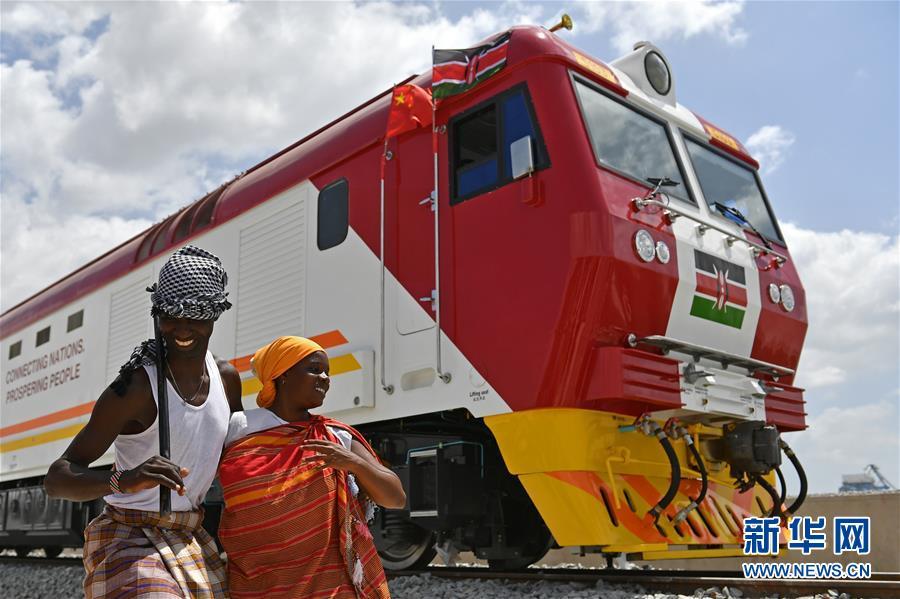 2017年1月11日,在肯尼亚蒙巴萨,当地民众在中国承?#39057;?#33945;内铁路?#30528;?#20869;燃机车旁载歌载舞。蒙内铁路是肯尼?#20146;远?#31435;以来最大的基础设施工程,项目累计为当地直接创造逾4.6万个工作岗位。 新华社记者孙瑞博摄