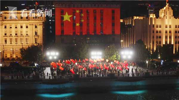 5.一面巨大的国旗投射在海关大楼上,参与快闪活动的市民群众挥舞手中的国旗与之呼应。摄影:杨光.jpg