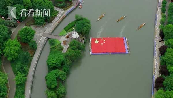 普陀快闪活动中,三艘龙舟护送着一面巨幅五星红旗在苏州河上缓缓前行。