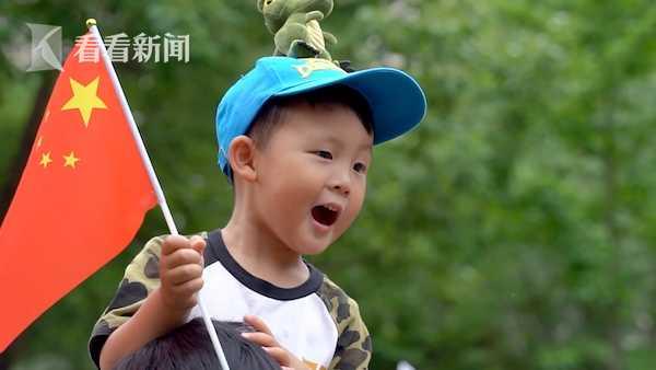 孩童跟着旋律挥舞手中的国旗。