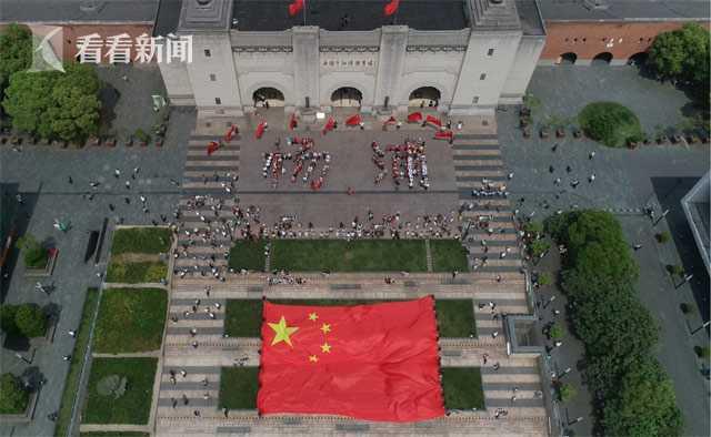 """兴奋的人们摆出""""杨浦""""字样,巨幅国旗在创智天地广场中央展开"""