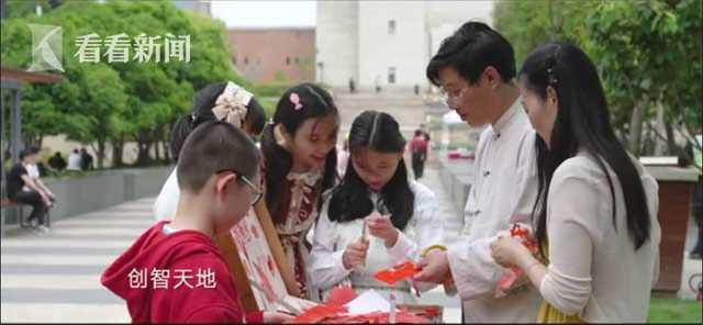 广场一侧,小朋友们围在花样经艺人旁学剪纸