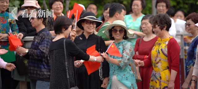 志愿者为来往市民分发小红旗