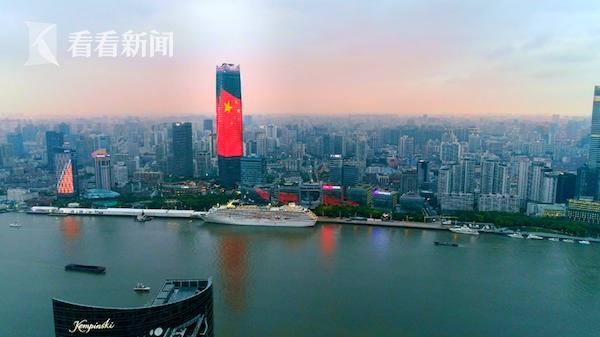 在落日余晖的映衬中,浦西第一高楼、白玉兰广场主楼的LED荧幕上亮起五星红旗