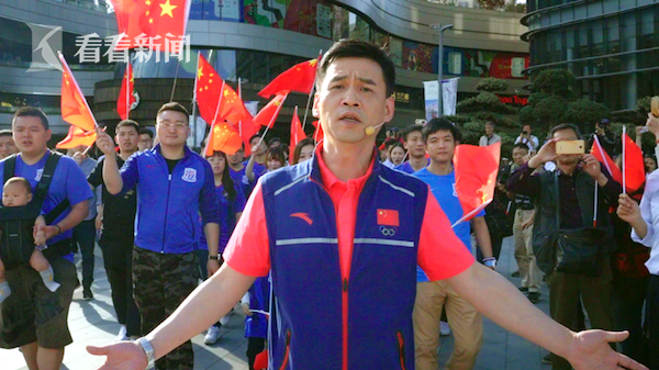 男子花剑世界冠军叶冲和高举国旗的上海绿地申花队球迷们一同加入快闪活动