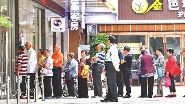老人们在银行门口自觉排队领取退休工资。新民晚报记者 孙中钦 摄