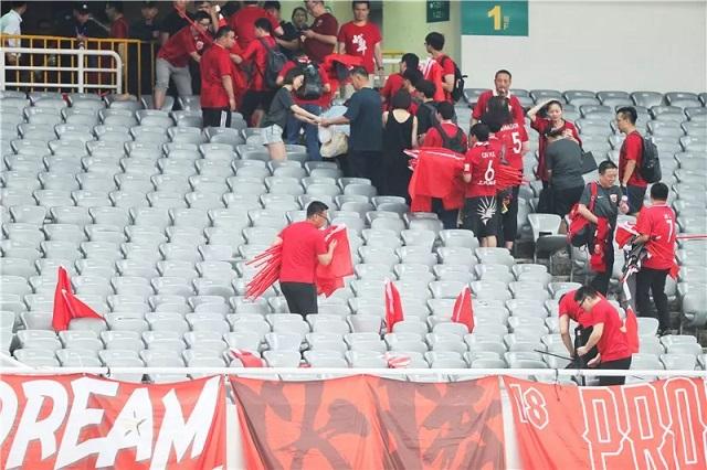 球赛散场后,志愿者正在收好红旗,恢复会场整洁。新民晚报记者 李铭珅 摄