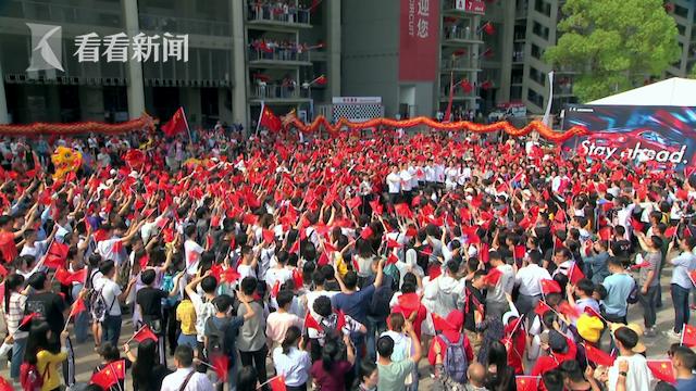 快闪活动现场,现场观众手举国旗高唱《我和我的祖国》