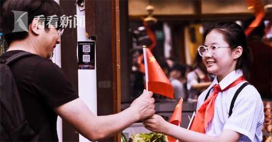 学生志愿者为古镇游客递上小国旗