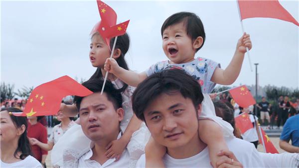 人们挥舞手中的旗帜,唱出心中的赞歌