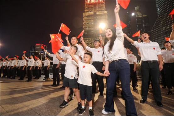 各行各业的代表挥舞着手中的国旗加入合唱