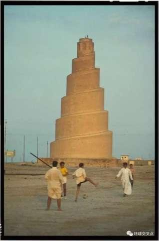 在伊拉克萨迈拉的大清真寺前,男孩们在踢足球,这里是巴格达迪的出生地
