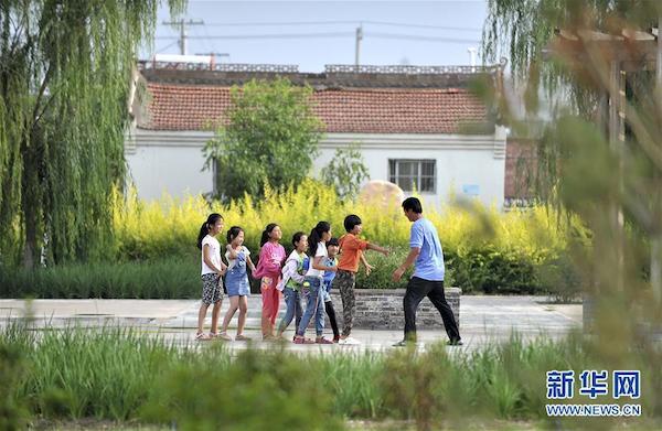 宁夏永宁县原隆村的孩子们在新居前的休闲广场上玩耍(2018年8月摄)。新华社记者 刘军喜 摄