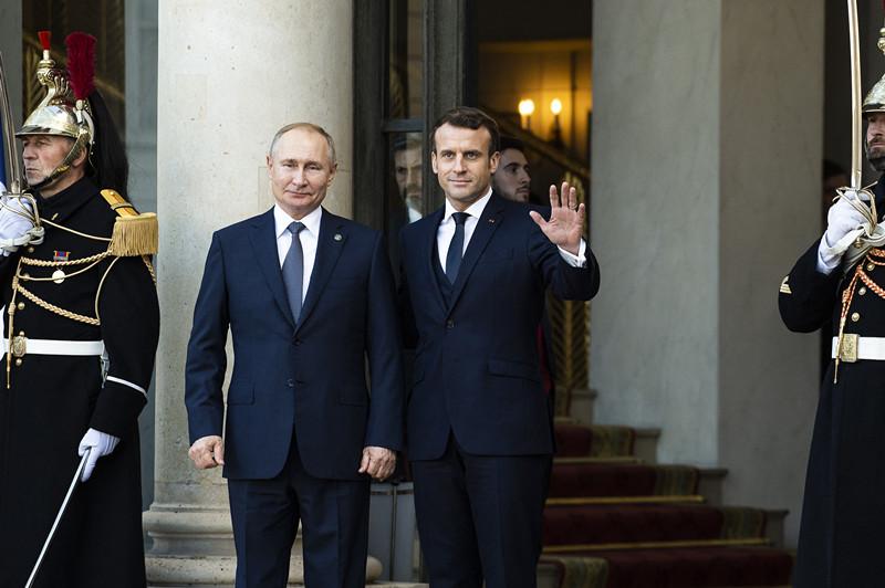 法国总统马克龙在巴黎爱丽舍宫欢迎前来参加四国峰会的俄罗斯总统普京