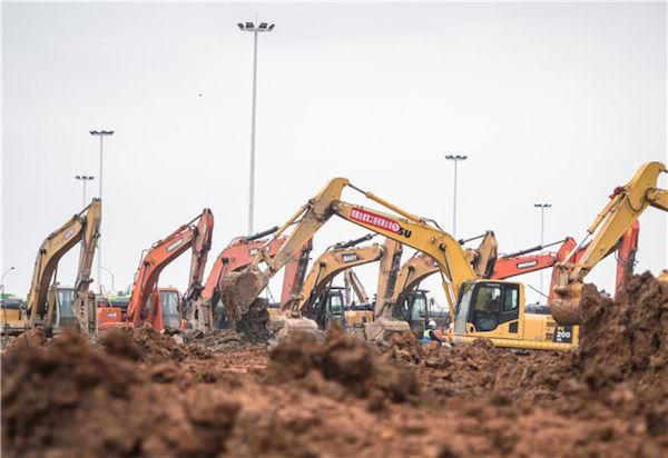 1月26日,在武漢雷神山醫院建設工地,大型機械加緊施工。新華社記者 肖藝九 攝