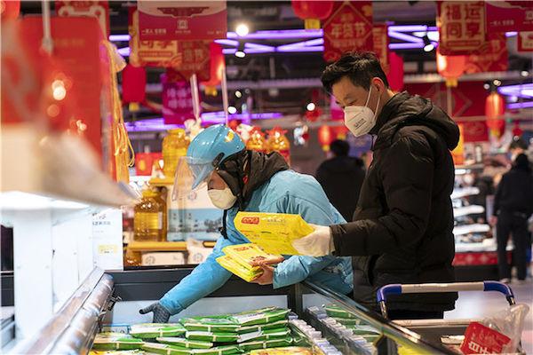 1月27日,武漢市民和外賣代購小哥在一家盒馬鮮生店內選購商品。新華社記者 熊琦 攝