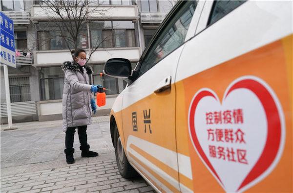 1月27日,武漢市武昌區糧道街曇華林社區干部在給配給社區使用的出租車消毒。新華社記者 程敏 攝