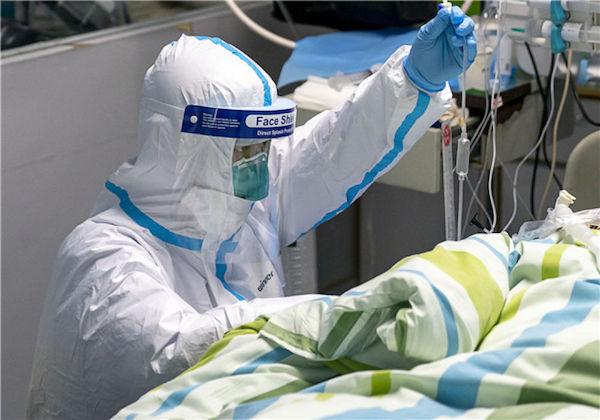 1月24日,在武漢大學中南醫院重癥隔離病房,醫護人員為病人治療。新華社記者 熊琦 攝