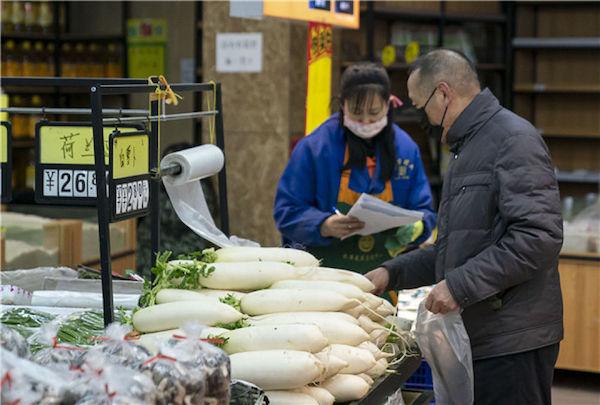 1月27日,武漢市民在菜場內選購蔬菜。新華社記者 熊琦 攝