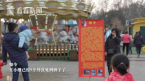 王小滑在大街上舉著牌子找孩子